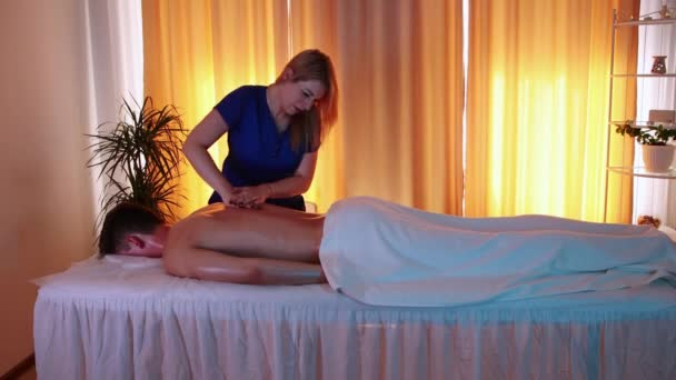 Masážní sezení v lázeňském centru - žena lékař masíruje své klienty zpět olejem