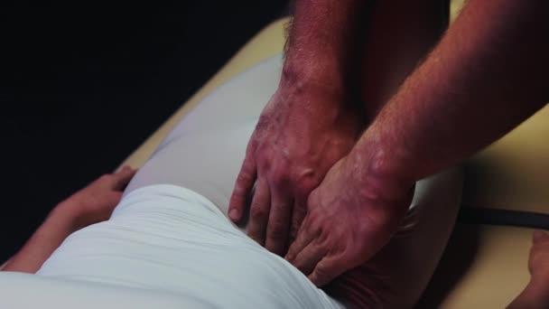 Nő fekszik a kanapén, és egy csontkovács dolgozik a testével - nyomja a gyomra oldalán