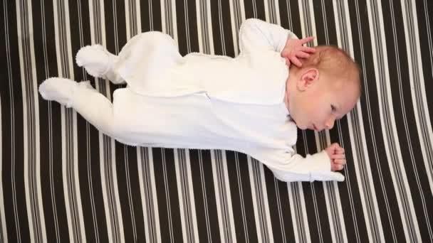 Malé novorozeně v bílém kostýmu ležící na zádech na pruhovaném prostěradle