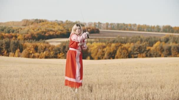 Junge Frau in langem Kleid steht auf dem Feld und spielt mit einem Schwert und lässt es fallen
