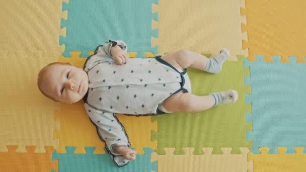 A kisfiú a hátán fekszik a pasztell szőnyegen.