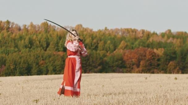 Feisty Frau im roten Kleid beim Training auf dem Feld - trainiert mit einem Schwert