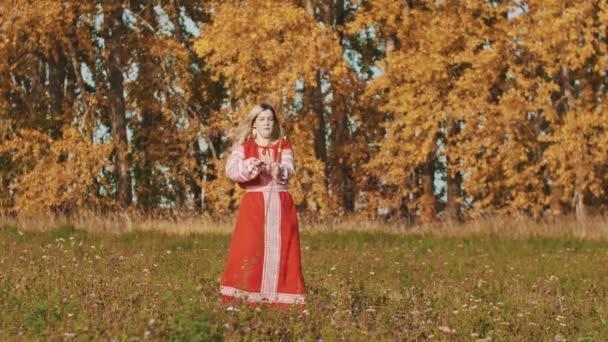 Feisty erwachsene Frau in rotem Nationalkleid dreht ein Schwert über sich selbst