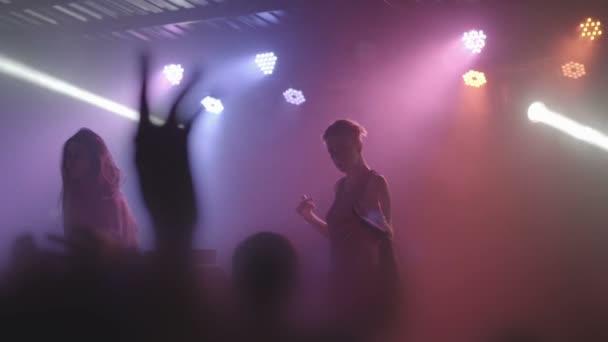Dvě krásné mladé ženy Dj hrát hudbu na mixovacím pultu v nočním klubu. Pozadí nelze rozpoznat lidí. Zpomalený pohyb