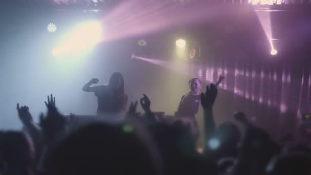 Due belle giovani donne Dj suonano la musica sulla console di mixaggio in nightclub. Contro lo sfondo di persone irriconoscibili. Slow motion