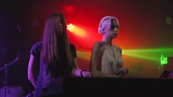 Dvě krásné mladé ženy Dj hrát hudbu na mixovacím pultu v nočním klubu