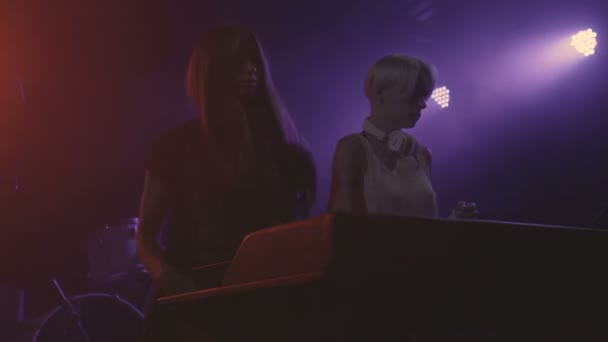 Two beautiful young women DJ play the music on the mixing console in the nightclub slow motion