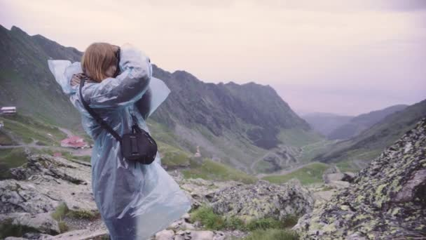 A young woman hiker climbs mountains and photographs landscapes on camera. Transfagarasan, Carpathian mountains in Romania