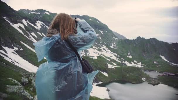 Tramp mladá žena leze hory a fotografie krajiny na fotoaparátu. Transfagarasan, Karpaty v Rumunsku