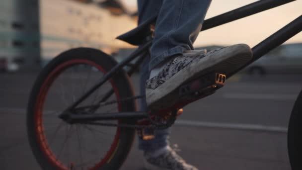 A kerékpárosok lovagolni bmx szabadban naplementekor. Lassú mozgás közelről