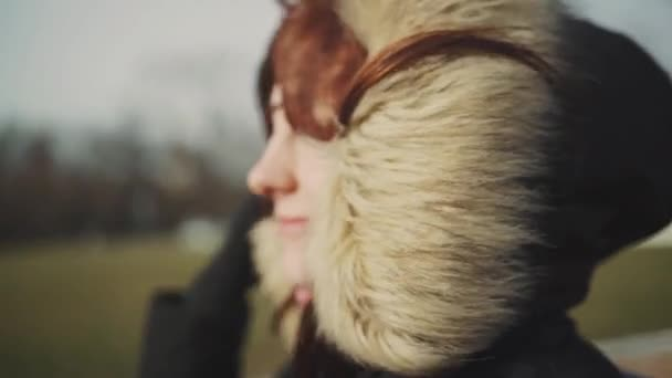 Closeup portrait of a young beautiful red-haired woman outdoors. Girl in a warm fluffy jacket