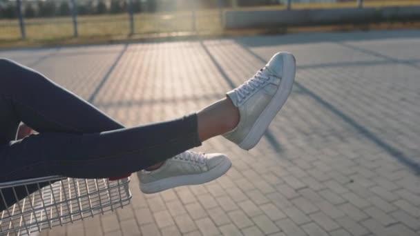 szerelmesek egy szupermarket parkolójában egy bevásárlókocsival a boltból naplementekor. Lassú mozgás.