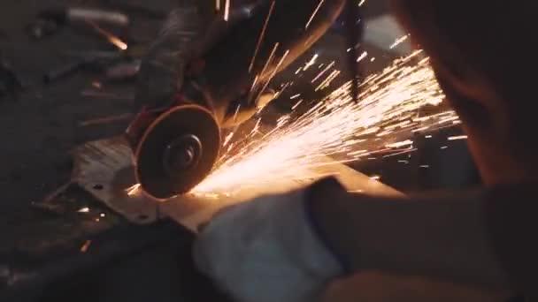 Člověk pracuje s kulatou pilou. Jiskry létají z horkého kovu. Muž tvrdě pracoval na oceli. Detailní záběr zpomaleného záběru v garáži