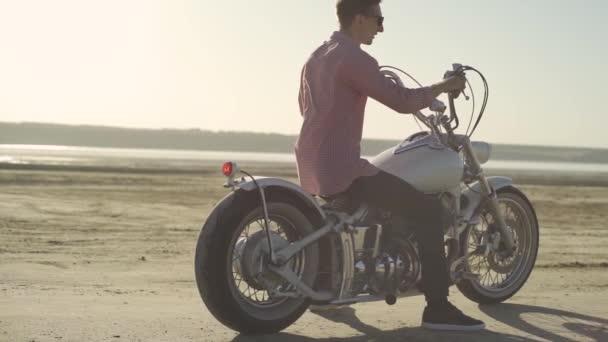 Motocyklista dělají pneumatiky vyhoření v poušti, zpomalené. Profesionální motocyklista drift a zapne na motorce na zemi, motorkář dělá trik na motorce