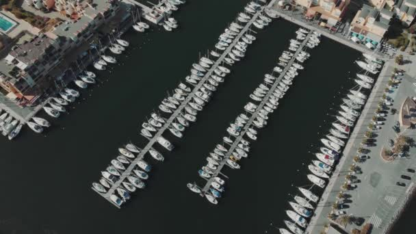 Aerial drone flying out over a marina for boats and tourist ships. Many yachts in French docks.