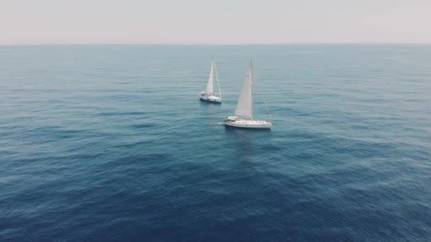 Letecký pohled na dvě jachty v oceánu, siluety plavců vedle jachet. Dronové záběry jachtingu na Baleárských ostrovech. Nepoznatelní lidé na jachtách