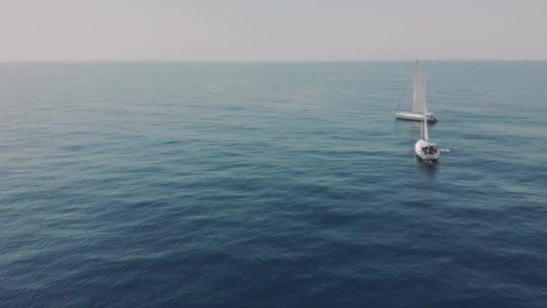Aerial View két jacht az óceánban, sziluettje úszók mellett jachtok. Drónfelvételek a jachtozásról a Baleár-szigeteken. Felismerhetetlen emberek a jachton.