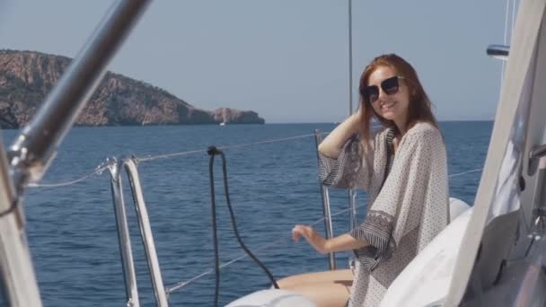 Beautiful woman on a yacht enjoys the journey on the background of the islands of Ibiza or Mallorca. Luxury yacht near the balearic islands