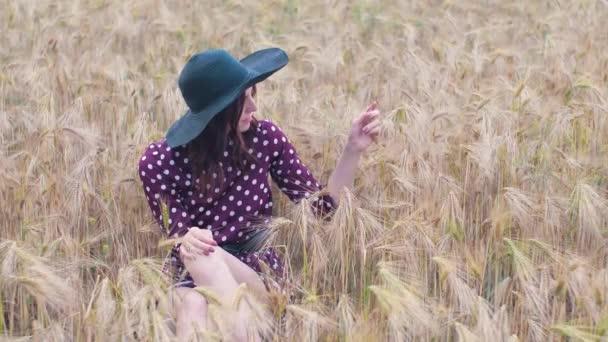 Porträt einer attraktiven Frau im Gras bei Sonnenuntergang. Schöne junge Frau geht in einem Weizenfeld. Zeitlupe