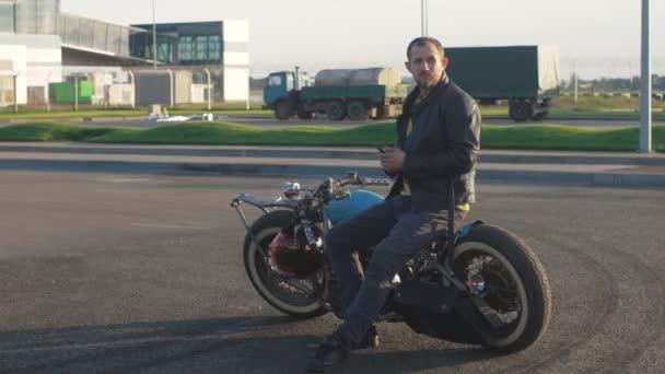 Mladý muž s chytrým telefonem v rukou na vlastní bobber motocykl na ulici při západu slunce, zpomalení.