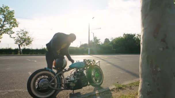 Mladý stylový motocyklista jde na své vlastní bobber motocykl na ulici silnici při západu slunce, zpomalení. Motorkář jezdit jeho ručně vyrobené vlastní kolo