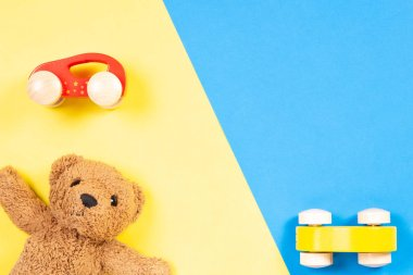 Colorful toys background with wooden cars and teddy bear