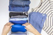 Photo Woman hands tidying up kids clothes in basket. Vertical storage of clothing, tidying up, room cleaning concept