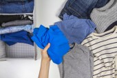 Photo Vertical storage of clothing, tidying up, room cleaning concept. Hands tidying up and sorting kids clothes in basket.