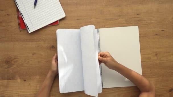 A srác lapozgat a jegyzetfüzetben. A gyerek házi feladatot csinál, üres lapokat böngészik a füzetben. Felülről lefelé