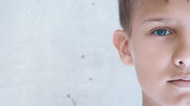 Chlapec se dívá přímo do kamery. Polovina obličeje. Dítě blízko Grunge šedé zdi