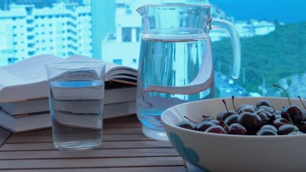 Léto, dovolená, zdravá výživa. Dětská ruka vzít sladké třešně z talíře u otevřených knih na stole na balkóně. Video 4k