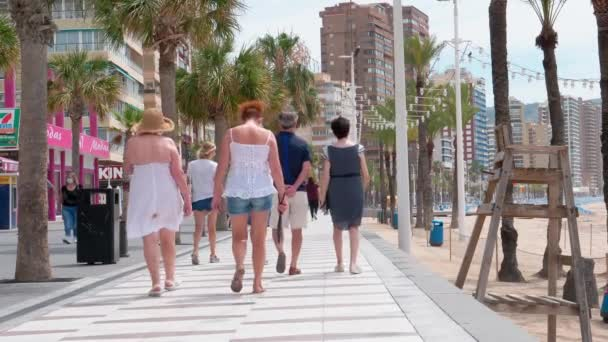 Benidorm, Spain, 14 June, 2020: People enjoy sunny day in Benidorm Levante beach promenade. Popular spanish resort after Coronavirus pandemic lockdown