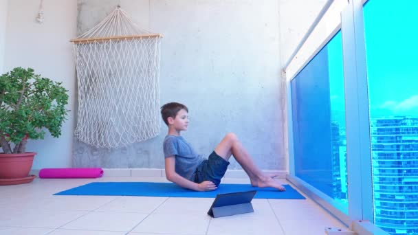 Boy doing sport exercises while watching video lesson online on tablet computer on balcony. Sport, healhty lifestyle, active leisure at home