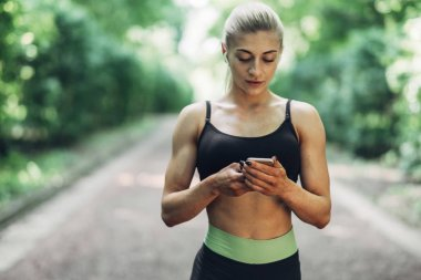 Woman Runner in the Summer Morning Park Listening to Music on Smartphone Using Bluetooth Earphones. Female Fitness Girl Jogging on Path Outside.