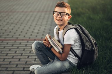 Portrait of a Little Boy in White T-Shirt and Jeans Holding Books in Hands