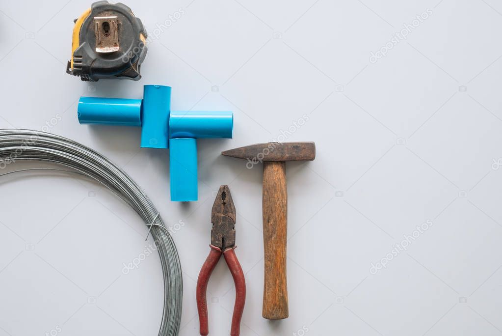 Tools for home repair with rust pliers, hammer, pipe, wire, meas