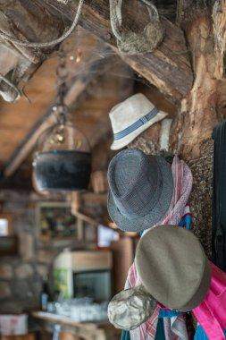 Detail closeup of few old hats hanging from a beam in an old farm shed turned restaurant
