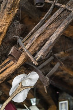 Detail closeup of an old white hat hanging from a wooden twig in an old farm shed turned restaurant