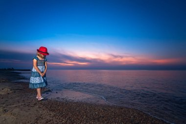 Cute little Caucasian girl walking slowly on the sea shore at sunset in summer