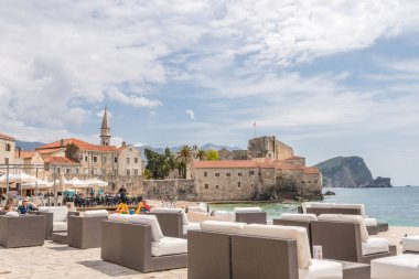 Budva, Montenegro - April 2018 : Large empty lounge chairs waiting for tourists on the beach outside a cafe and restaurant
