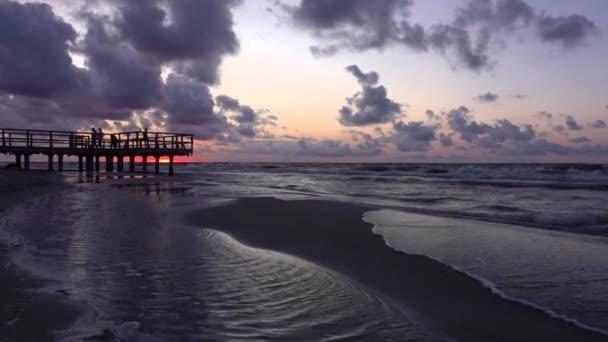 Video eines Sonnenuntergangs über einem Holzsteg am Meeresstrand in Sarbinowo, Ostsee, Polen