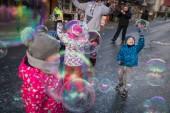 Karpacz, Polsko - února 2018: Děti snaží chytit obří mýdlové bubliny na hlavní ulici high v městečku Karpacz, polský zimní lyžařské středisko