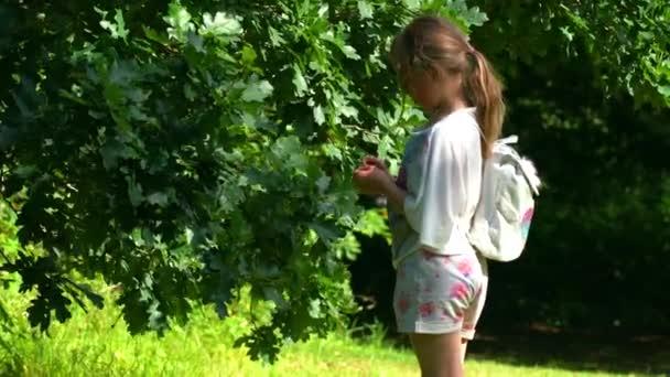 Roztomilá Kavkazská dívka s malým bílým batohu trávení čas venku v lese