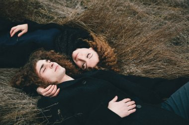 adult son and mom with curly hair laying on the straw field
