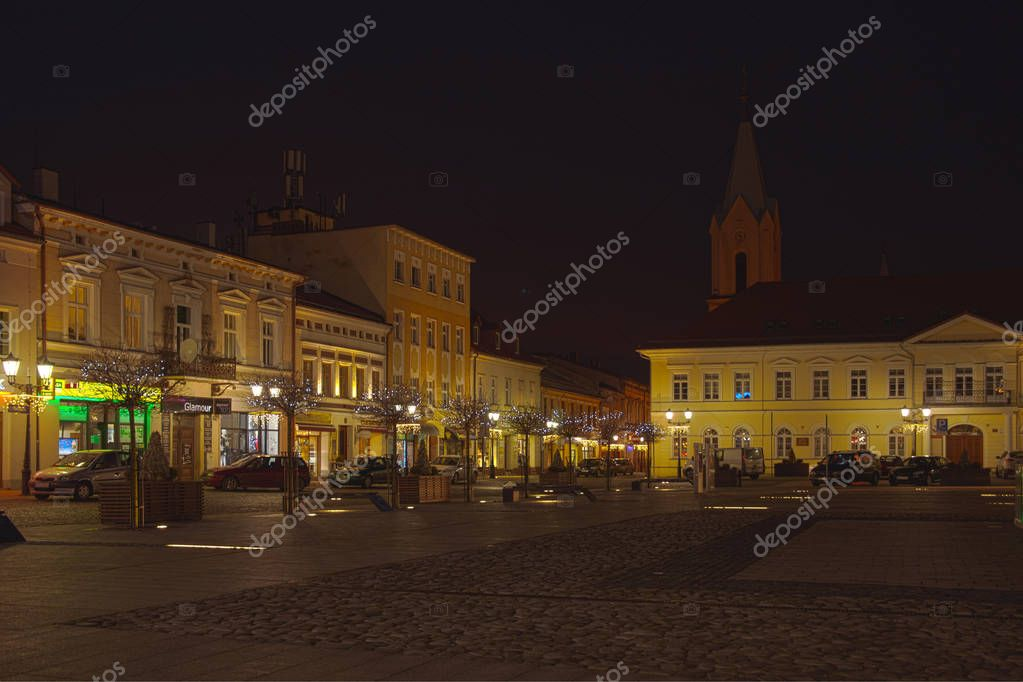 Oswiecim, Poland - December 24, 2017: The main square of the city at night. Tenements around the main square. Meeting place for people, the central point of the city. Architecture in Oswiecim.