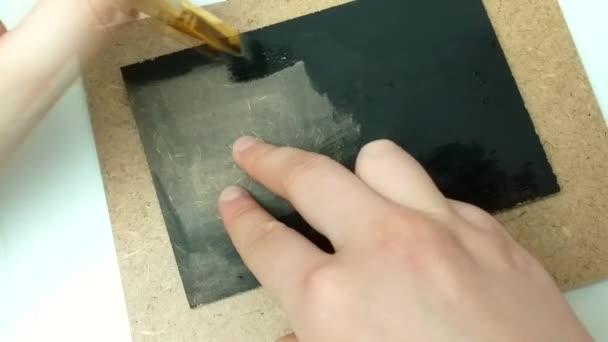dívka maluje plátno černou gouache barvou. Ručně vyráběná tableta pro psaní textu.