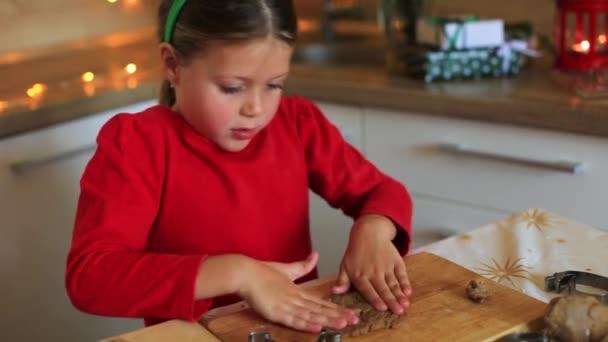 Glückliches kleines Mädchen bereitet am Vorabend von Weihnachten Plätzchen zu.