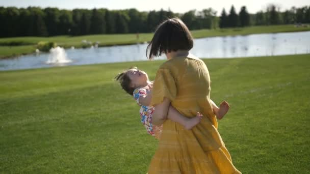 Mother spinning little daughter on green meadow