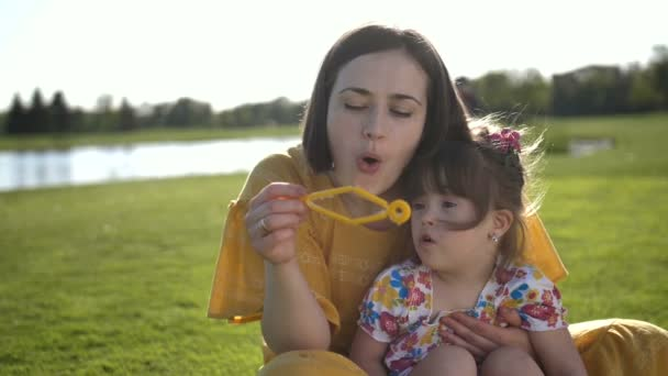 Mom and special daughter blowing bubbles in park