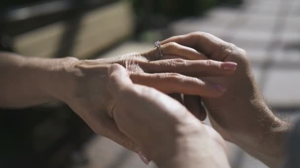 Senior hands during engagement with diamond ring